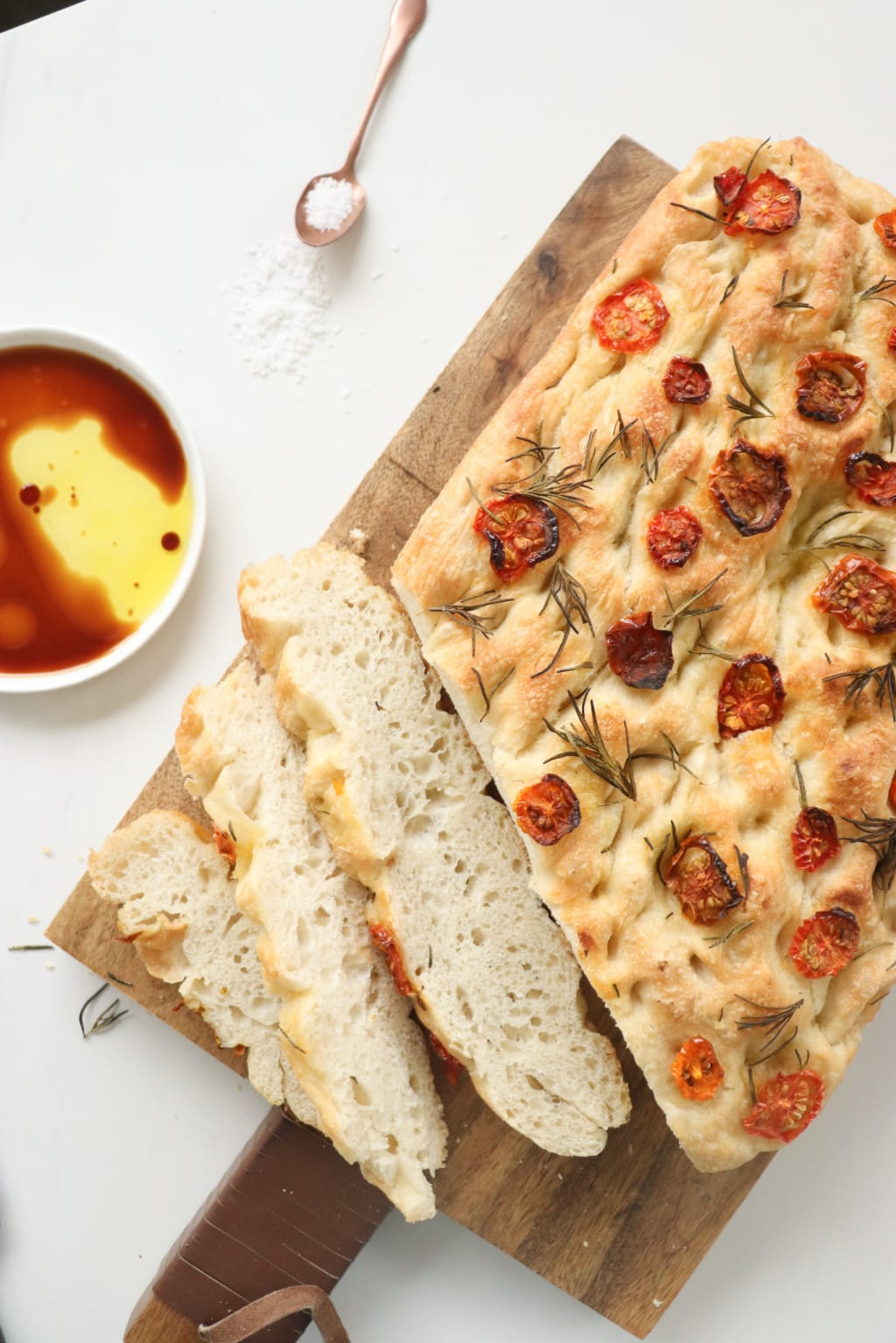 5-ingredient focaccia bread made with all purpose flour, salt, yeast, water, and olive oil topped with sundried tomatoes and rosemary placed on a wooden cutting board with a white dish beside it of balsamic vinegar.