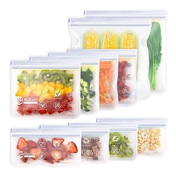 Plastic food storage bags with fruits and vegetables inside on a white background