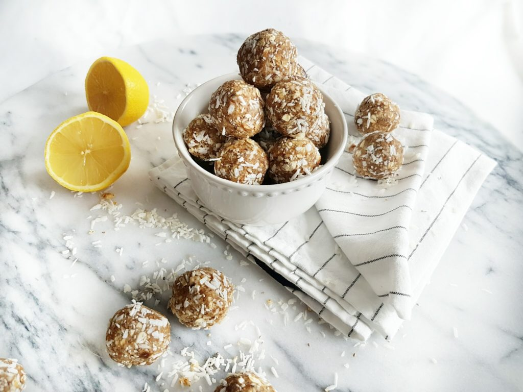 Lemon bluss balls in a white bowl over a white food photography board. Ingredients include: lemon, dates, almonds, shredded coconut, oats