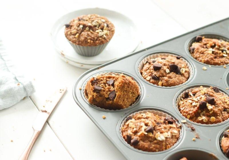 Oat flour pumpkin muffins in a muffin tin over a white food photo board. Ingredients include: oat flour. pumpkin puree, chocolate chips, peanut butter, pumpkin spice.