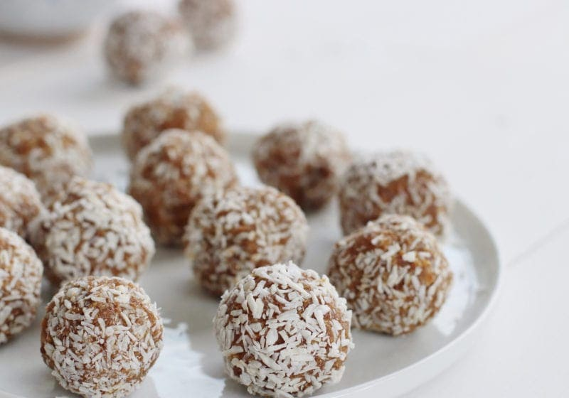 Salted caramel energy balls on a white plate over a white food photography board. Ingredients include: cashews, almonds, dates, vanilla, salt, shredded coconut.