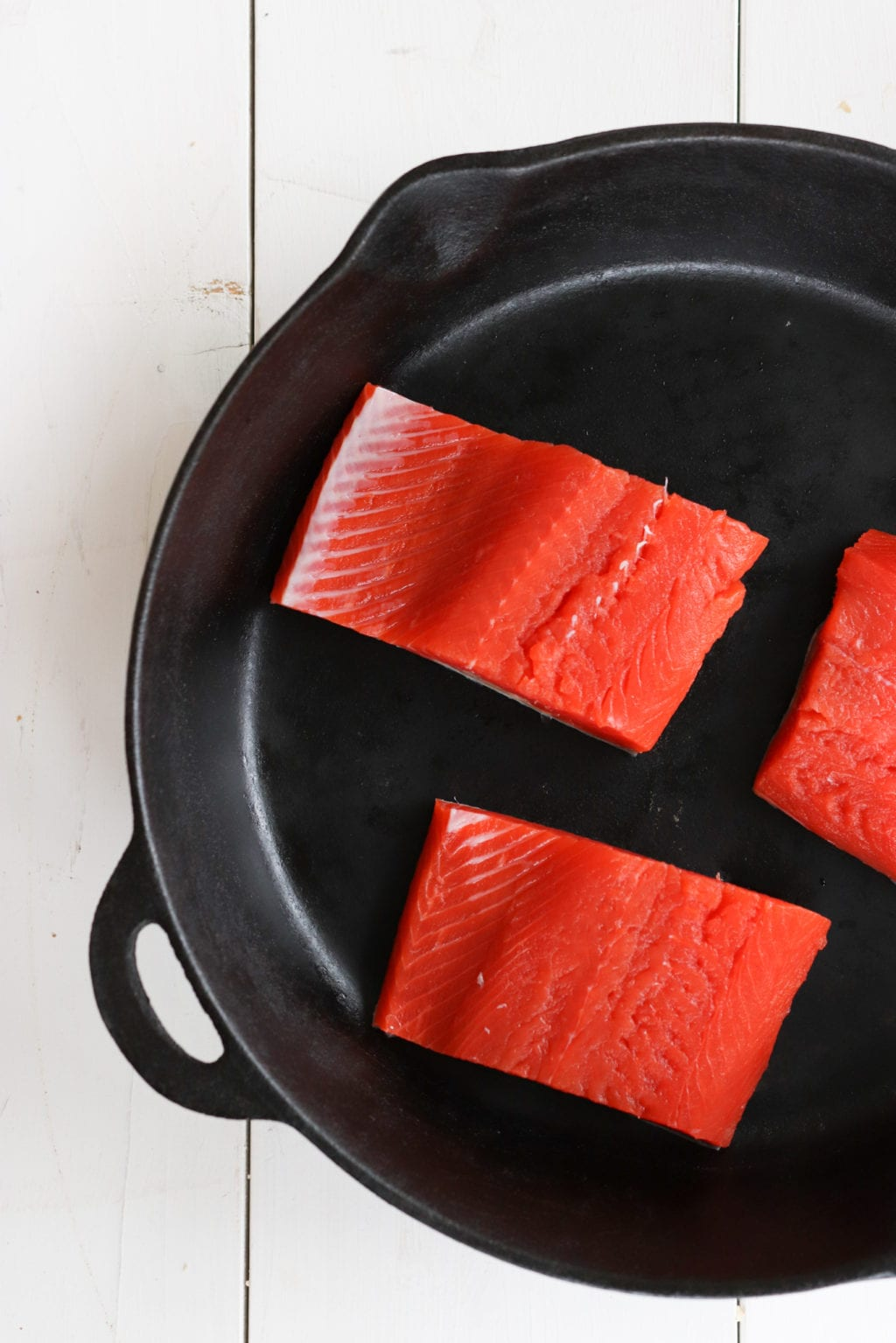 Raw salmon on a cast iron skillet over a white painted wood food photography board.