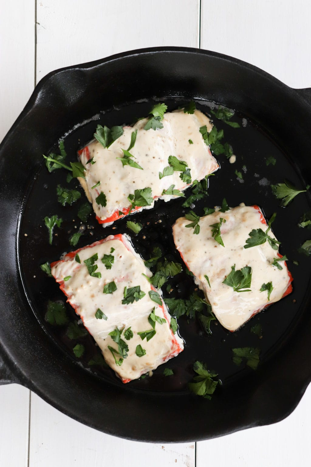 Miso Oven-Baked Salmon on a cast iron skillet over a white painted wooden food photography board. Ingredients include: salmon, plain greek yogurt, mayo, miso paste and salt and pepper.