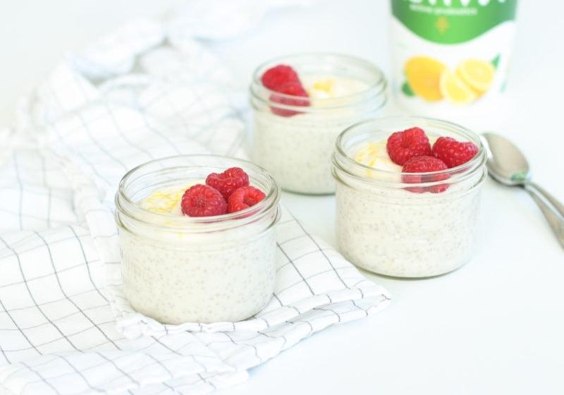Lemon coconut chia pudding in mason jars over a white surface. Ingredients include: lemon yogurt, full fat coconut milk, lemon zest, chia seeds, berries.