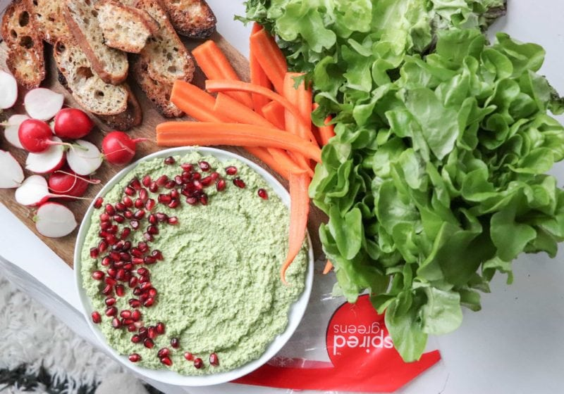 Edamame dip in a white bowl surrounded by bread, carrots, and greens. Ingredients for dip include: greens, edamame, olive oil, garlic, lemon, salt and pepper.
