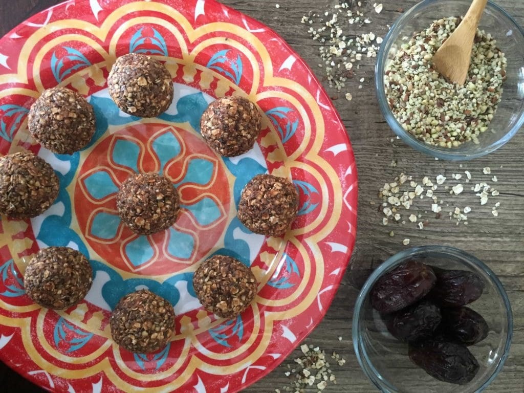 Peanut butter energy balls on a colourful plate over a wooden food board. Ingredients include: peanut butter, dates, hemp hearts, chia, flax, dates, cocoa, vanilla.