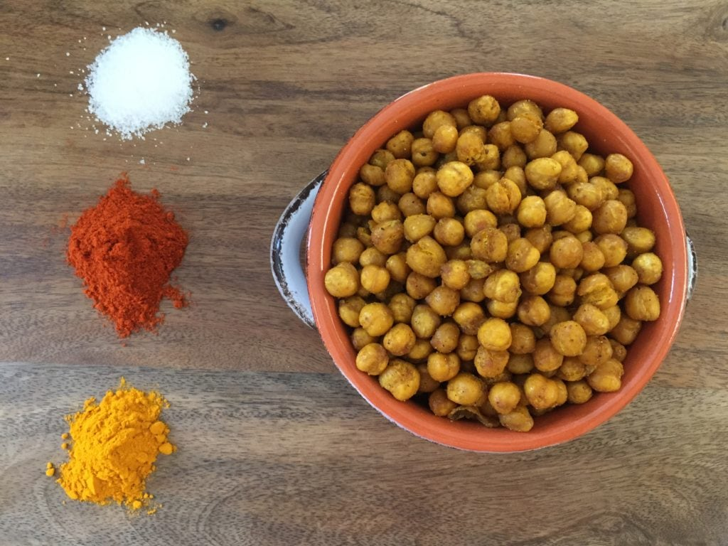 Baked Curried Chickpeas in a bowl over a wood food board. Ingredients include: chickpeas, curry spice, and avocado oil.