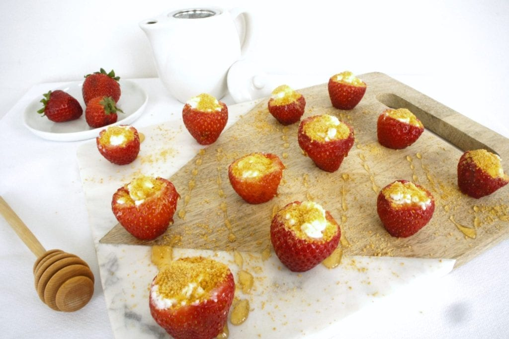 Strawberry cheesecake bites on a cutting board. Ingredients include: strawberry, goat cheese, graham cracker crumnbs.