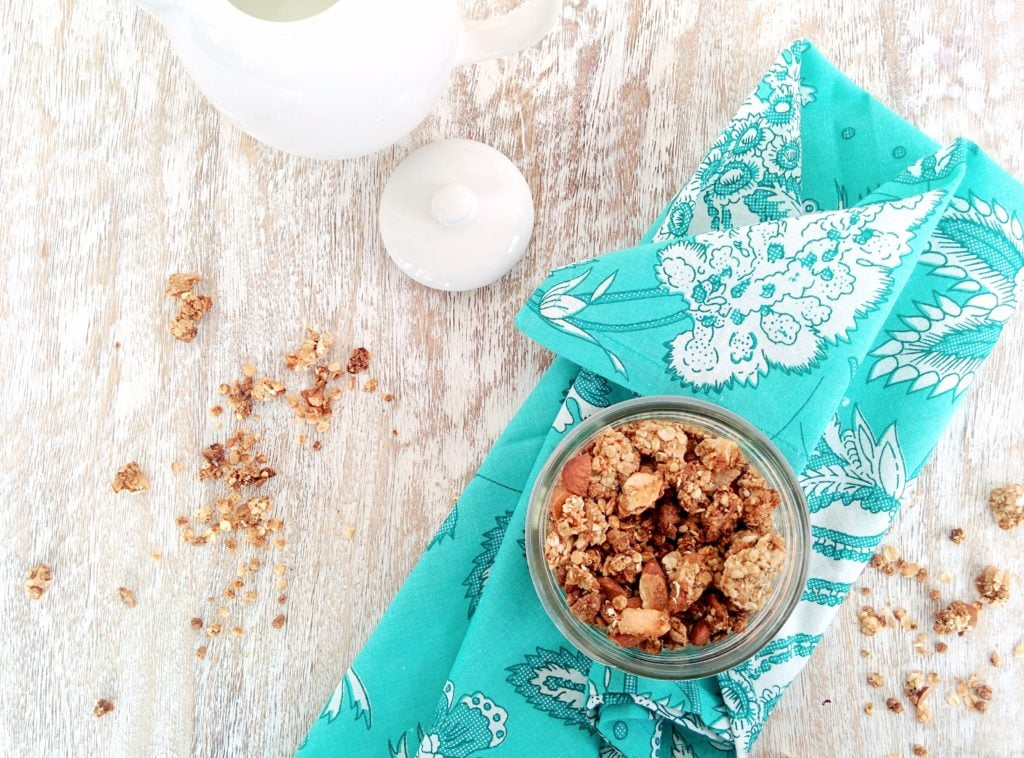 Health Nut almond granola in a mason jar over a blue kitchen towel on a wood surface. Ingredients include oats, bran buds, almonds, coconut, banana.