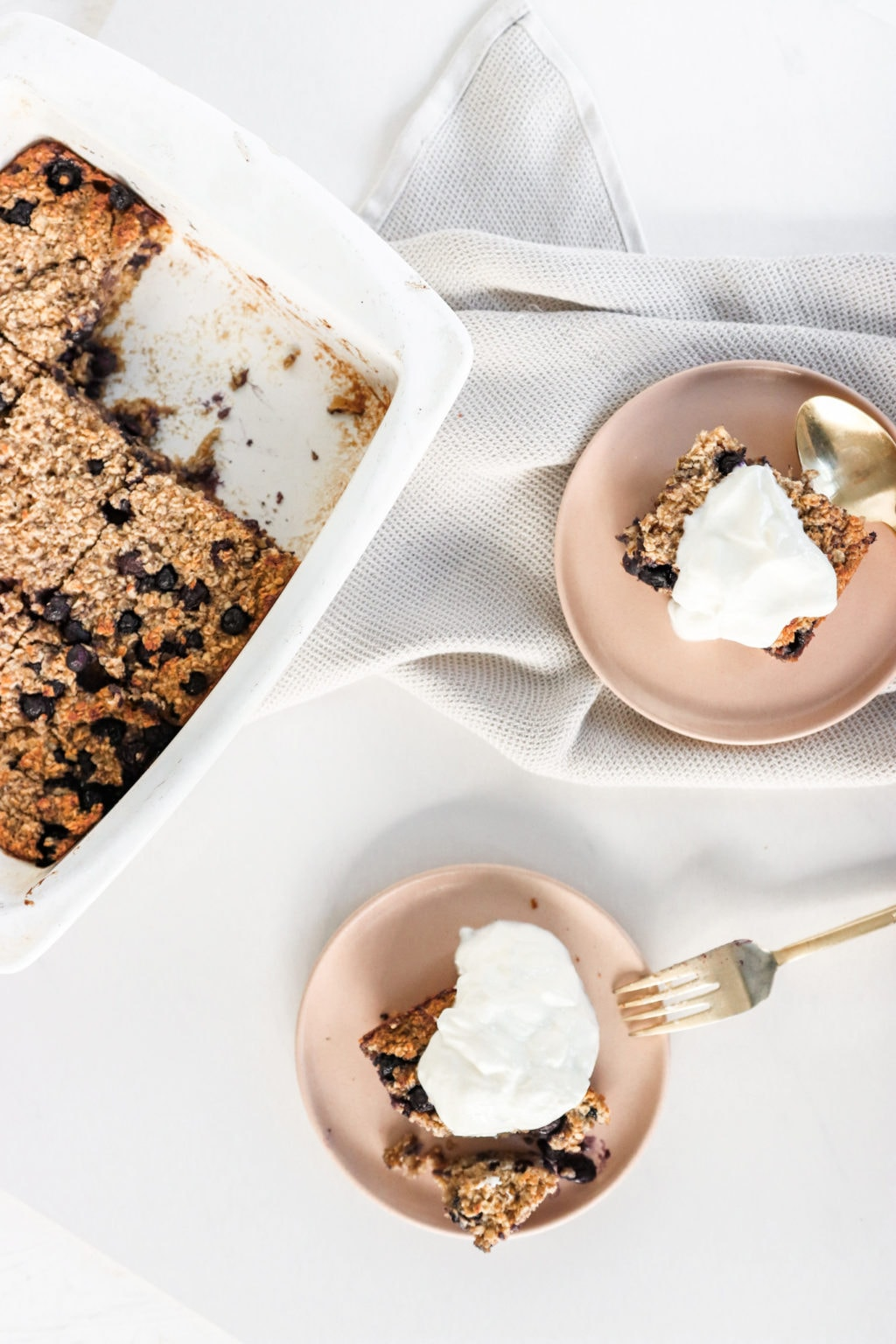 Blueberry baked oatmeal in a white dish cut up and served onto two pink plates topped with Greek Yogurt. Ingredients include: oats. blueberries, cinnamon