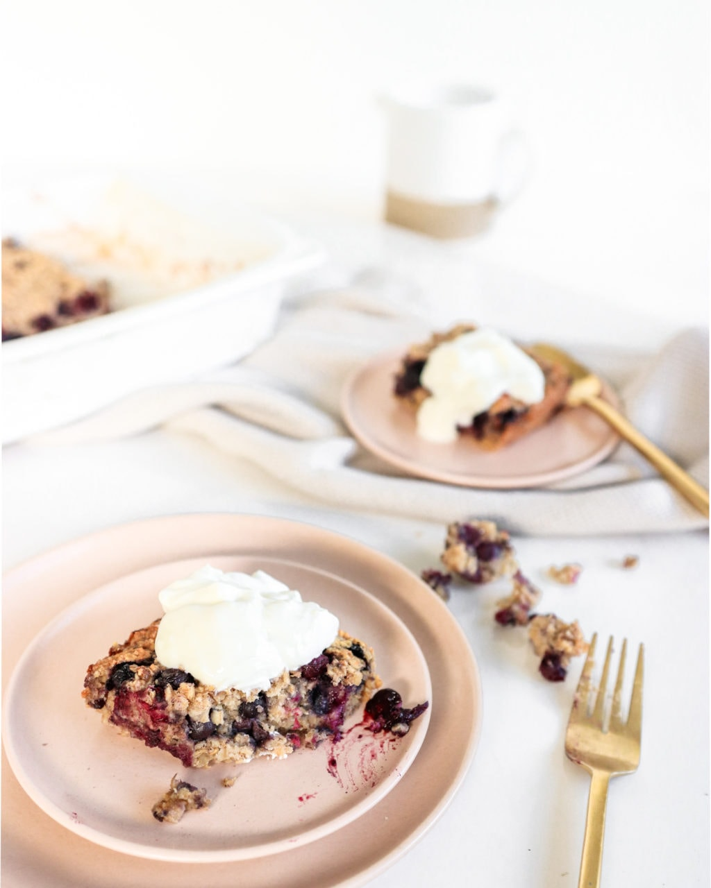 Blueberry baked oatmeal served onto two pink plates topped with Greek Yogurt. Ingredients include: oats, banana, blueberries, cinnamon, maple syrup.