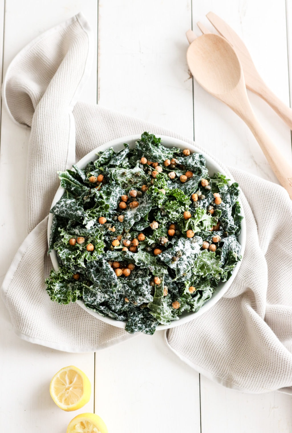 Chickpea kale caesar salad on a white plate over a neutral kitchen dish. Ingredients include: kale, chickpeas, capers, Greek yogurt, and garlic.