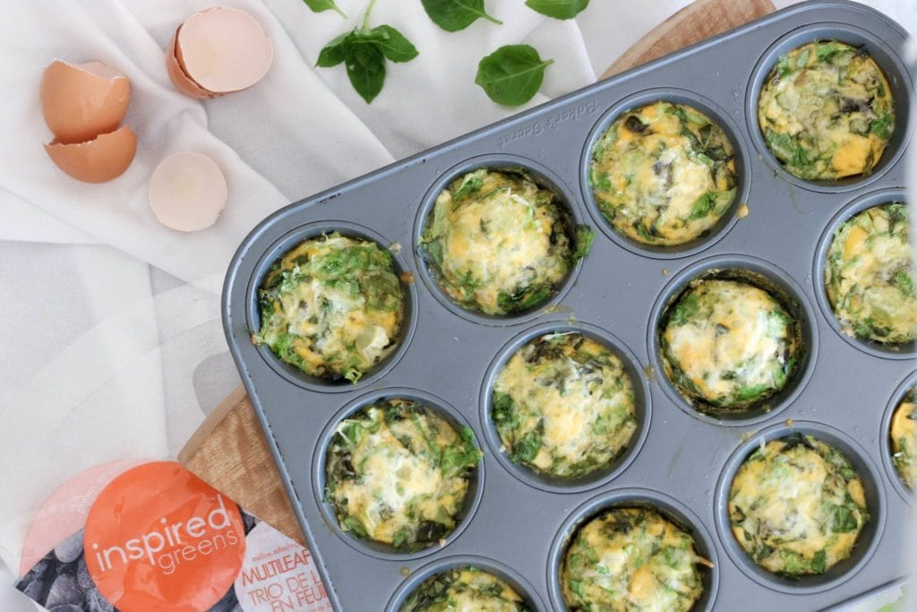 Muffin tin eggs over a white sheet surface. Ingredients include eggs, butter, onions, greens, basil, cheese.