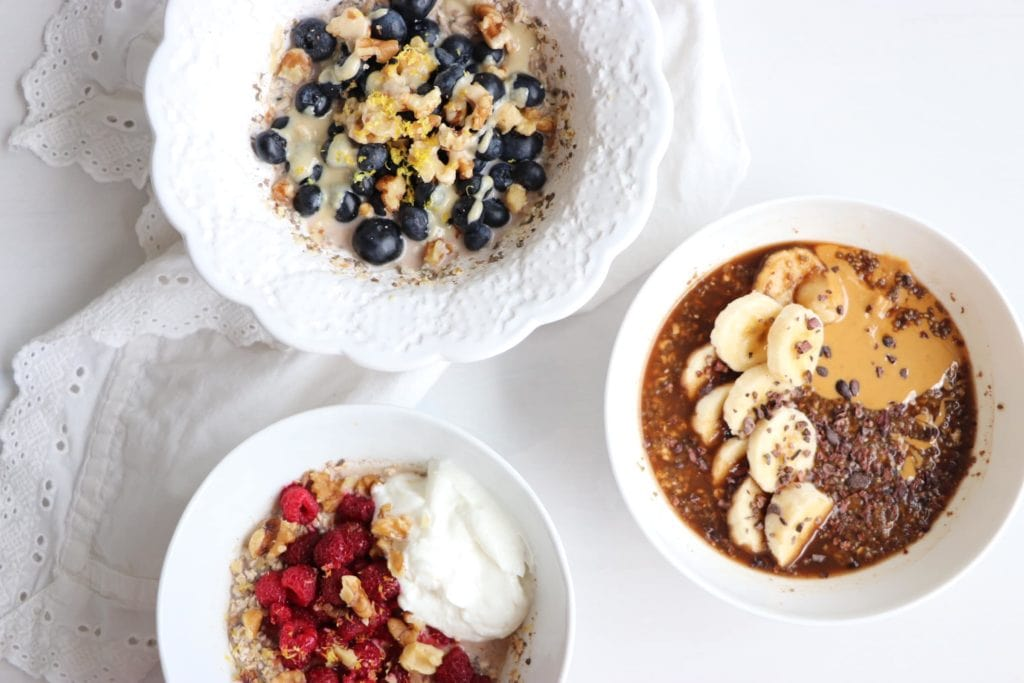 Oats 3 ways in three white bowls. Ingredients include oats, blueberries, banana, peanut butter, raspberries.