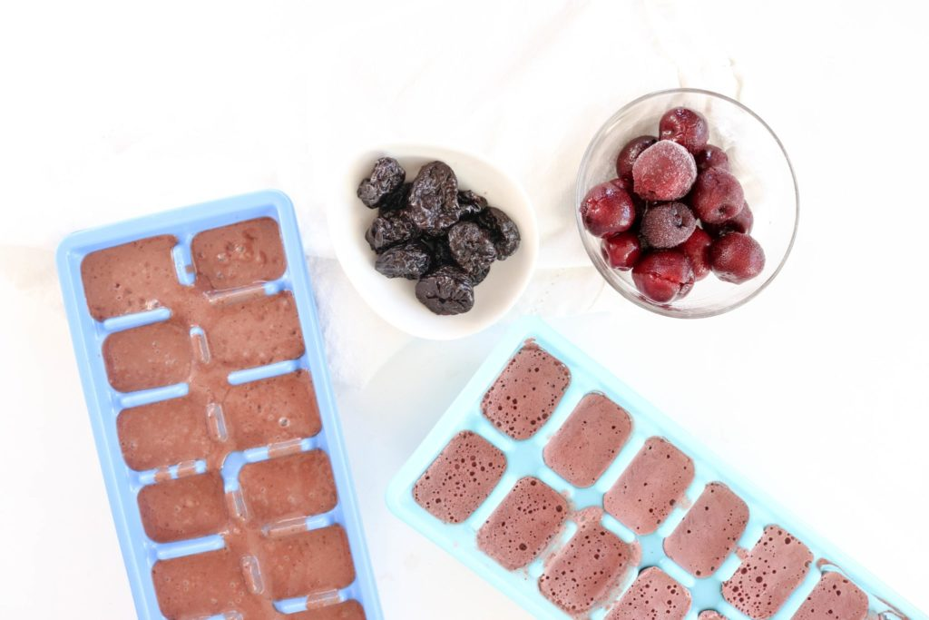 Smoothie cubes in a blue tray over a white surface. Ingredients include dark cherries, california prunes, Greek yogurt, cacao, sea salt.