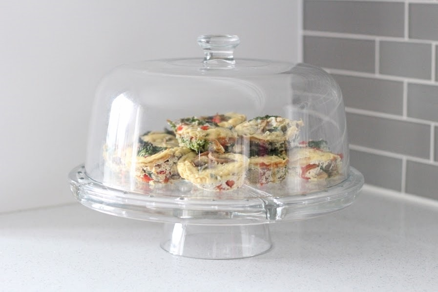 Muffin tin frittatas in a cake stand. Ingredients include eggs, milk, pepper, avocado oil, garlic, onion, mushroom, kale, cherry tomatoes, cheese.