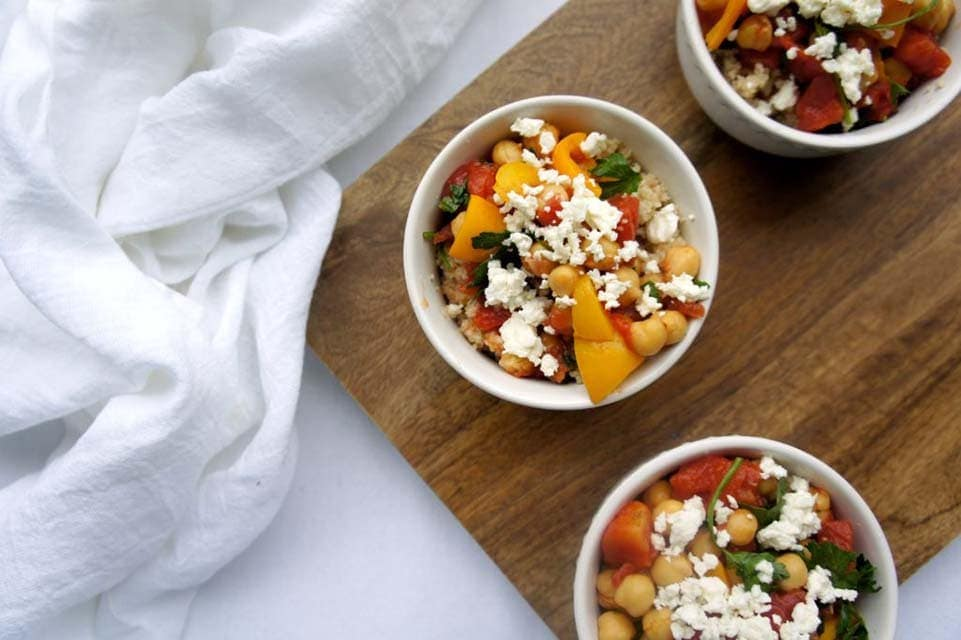 Three white bowls over a wooden food board filled with chickpeas, bell pepper, tomatoes, parsley, feta, and lemon.