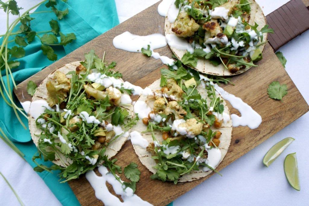 Roasted cauliflower chickpea tacos on a wooden food board. Ingredients include chickpeas, cauliflower, corn tortillas, arugula.