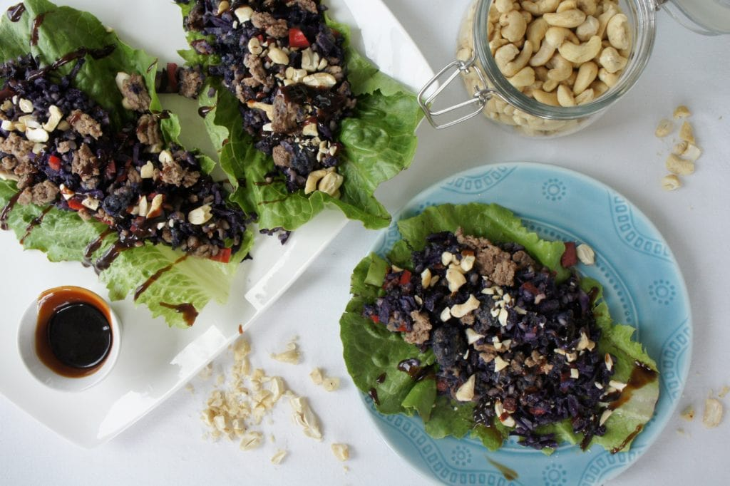Shanghai lettuce wraps topped with ground beef, mushroom, red pepper, purple cabbage, brown rice, cashews.