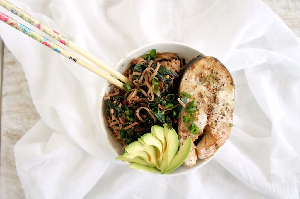 A white bowl over a white sheet filled with ingredients like salmon, avocado, noodles, swiss chard.