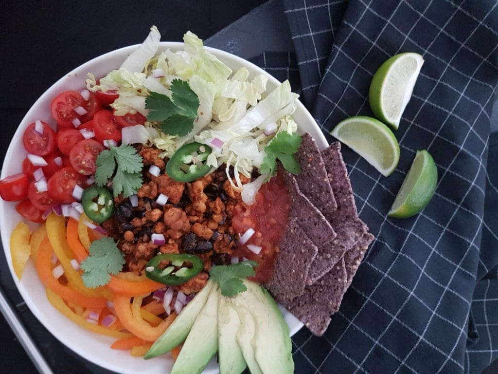 A white bowl filled with rice, tempeh, tortilla chips, bell pepper, avocado, jalapeno, beans, cherry tomatoes, onion over top of a navy checker kitchen towel.