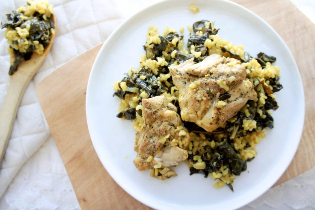 Turmeric lemon rice and chicken on a white plate over a wooden cutting board. Ingredients include rice, lemon, turmeric, chicken, and kale.