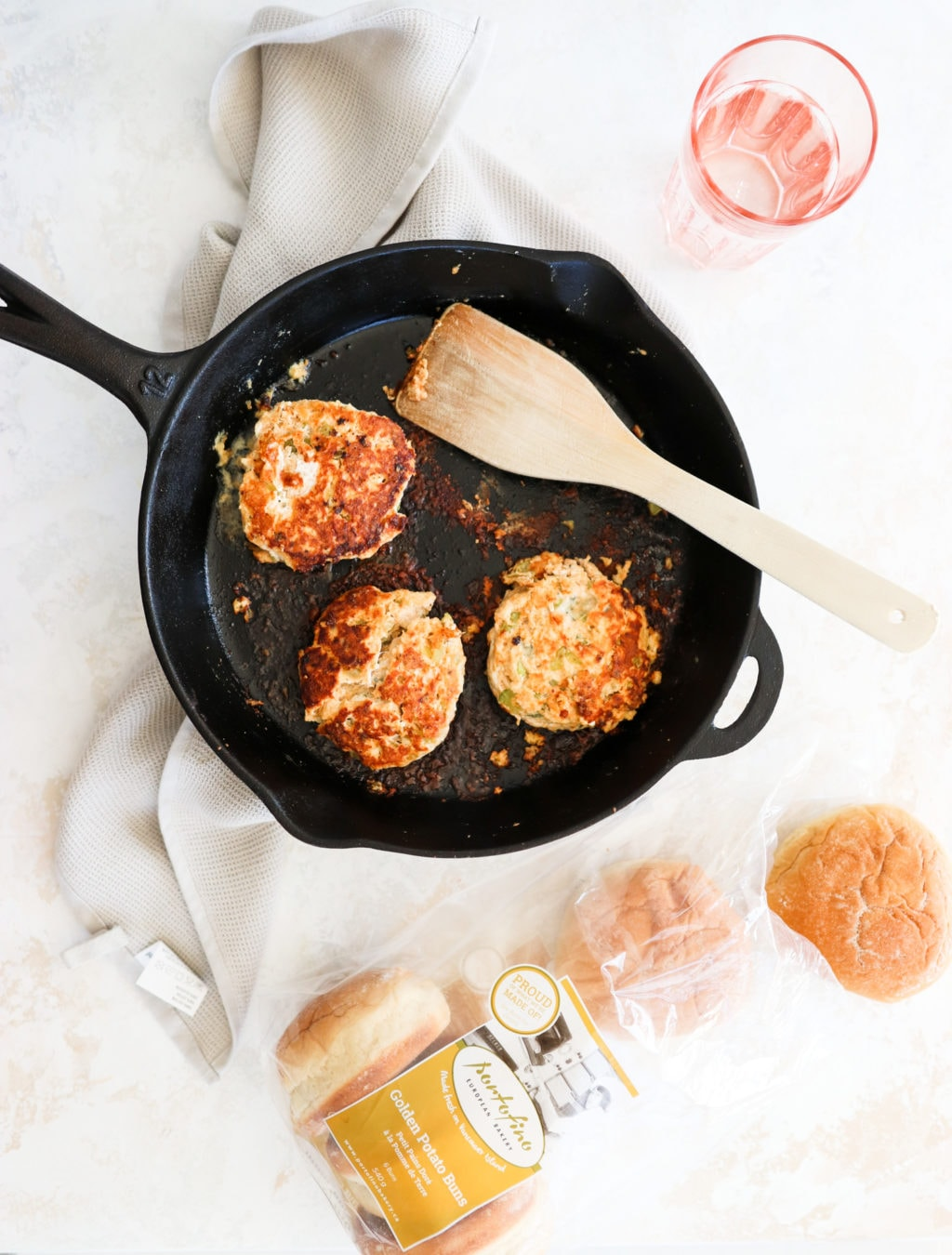 Three chicken patties sitting on a large cast iron skillet with a wooden spatula over a white surface with a bag of burger buns beside it.