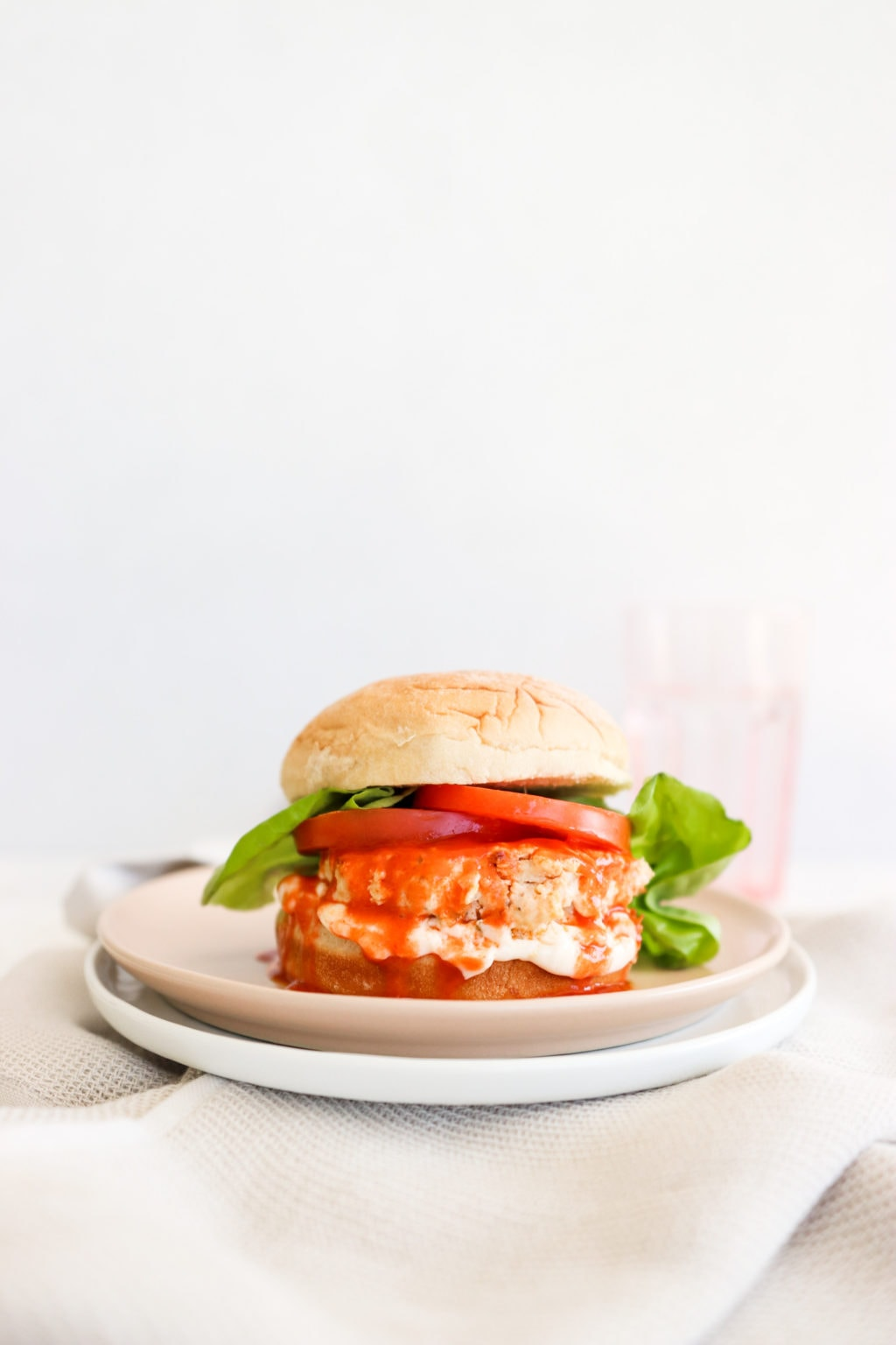 Buffalo chicken burger on a pink plate over a white plate sitting on a neutral coloured kitchen towel. Ingredients include: burger bun, buffalo chicken patty, lettuce, tomato, and hot sauce.