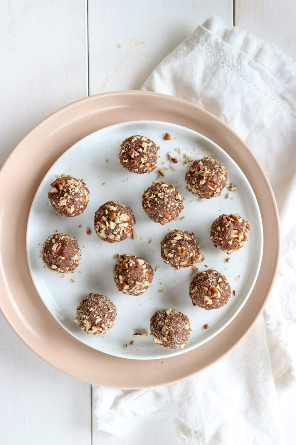 Pecan Pie Energy Balls neatly placed on a white plate over a pink plate over a white cloth. Ingredients include: pecans, dates, vanilla, cinnamon, salt.