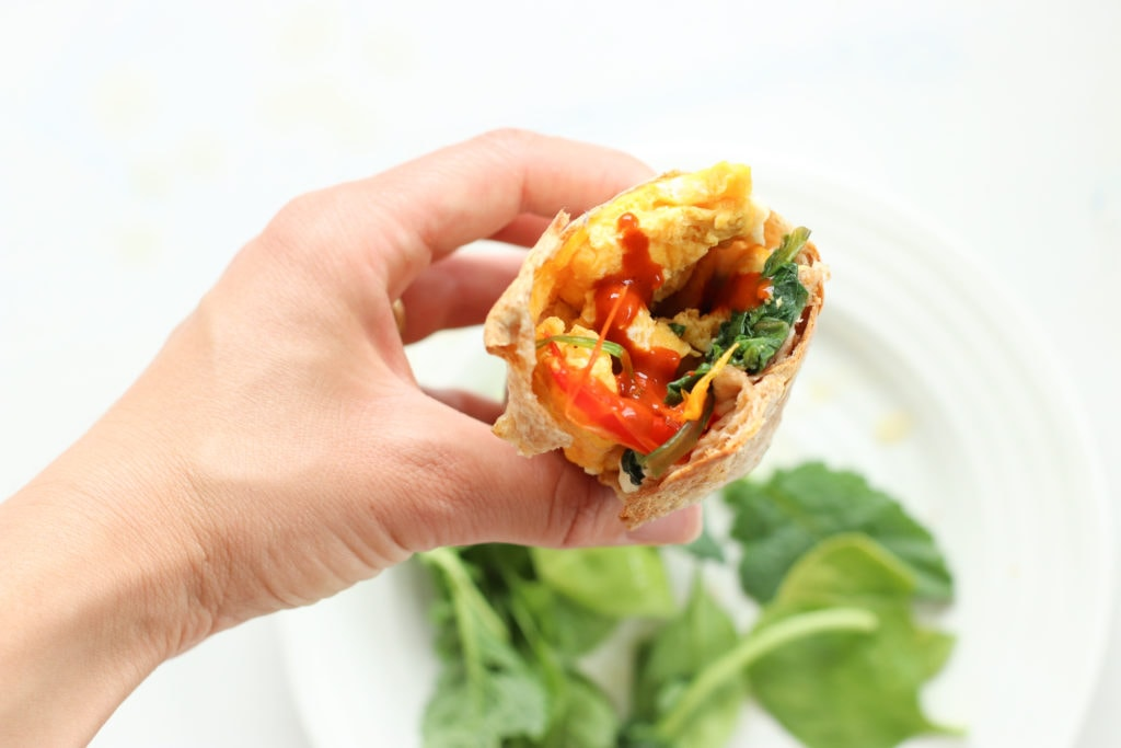 Lindsay Pleskot holding a Healthy Meal Prep Breakfast Burrito that has a bite out of it over a white plate that has greens. Ingredients include: whole grain wrap, eggs, spinach, bell peppers , feta, hot sauce.