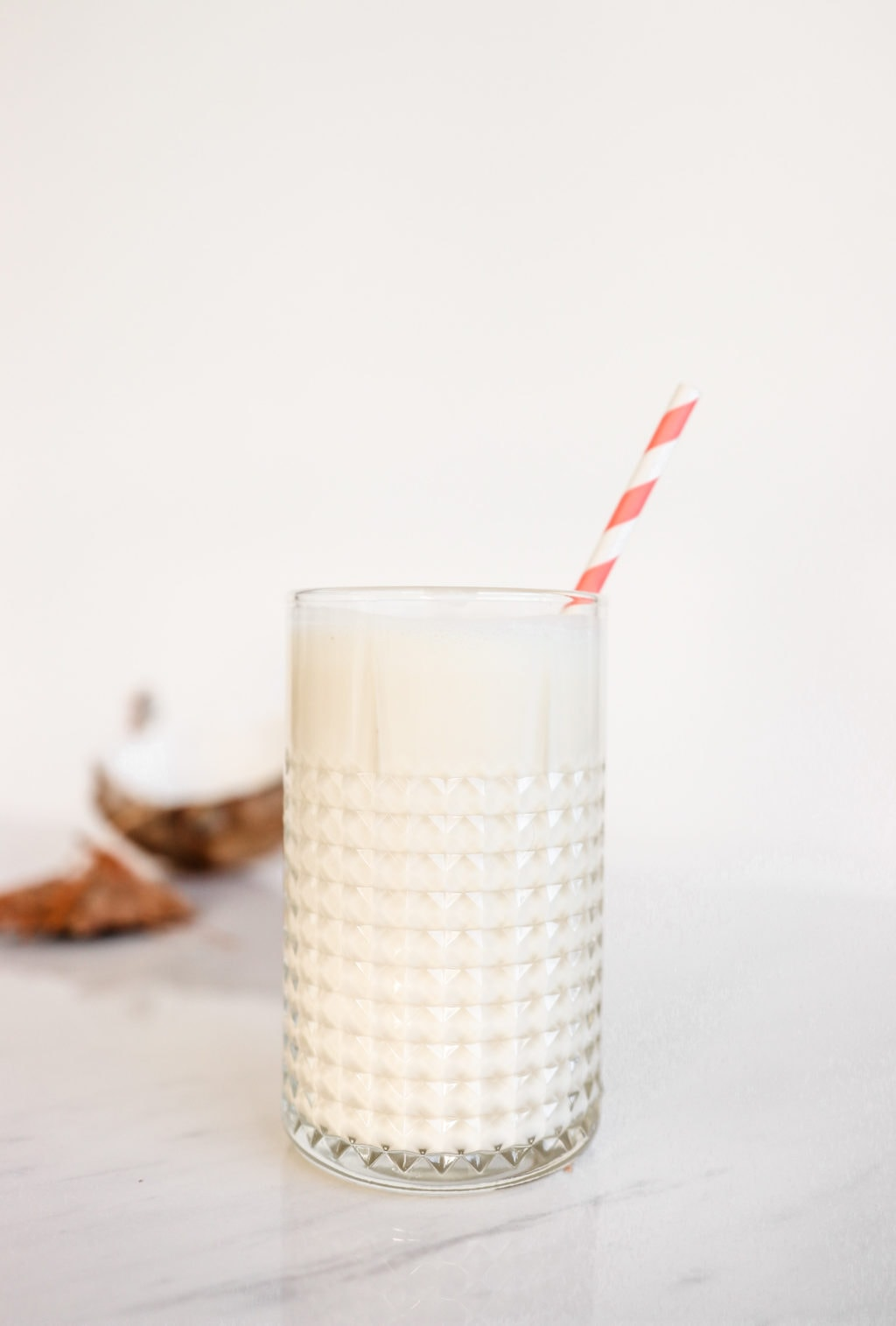 A pina colada smoothie in a glass with a pink and white striped straw on a white surface with a broken coconut beside it. Ingredients include coconut milk, pineapple, banana, and plain Greek yogurt
