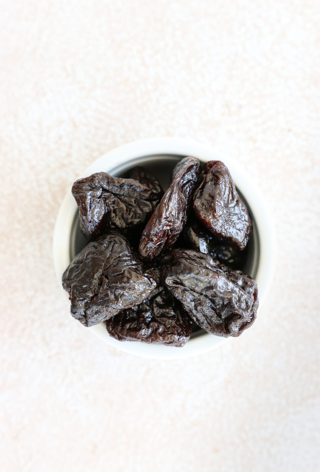 Prunes in a white bowl over a food photography board.