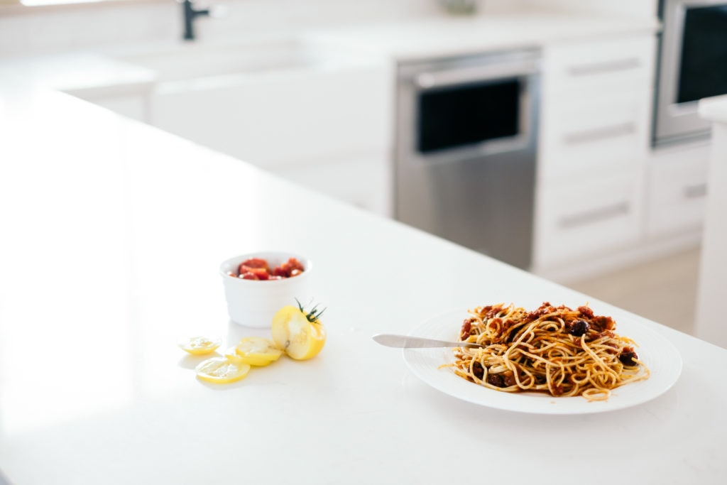 A white plate of spaghetti on a white counter in a white kitchen with a chopped yellow tomato beside it.