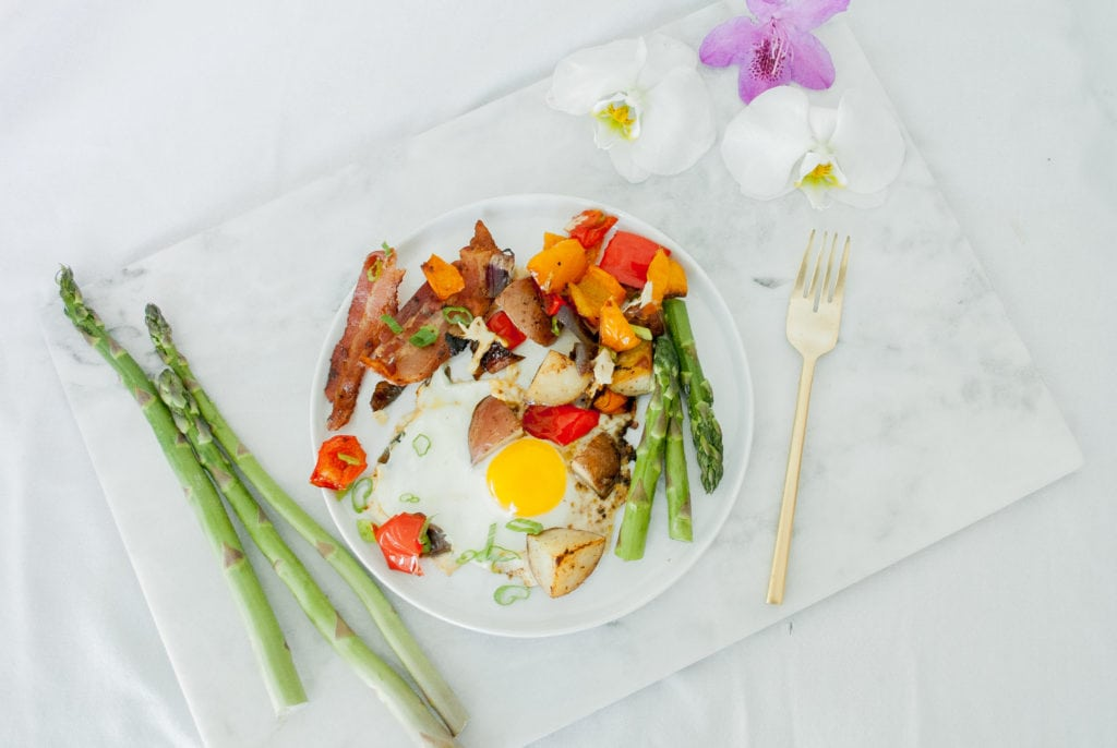 A marble slab with a plate of Healthy Sheet Pan Breakfast Bake on it and 3 sprigs of asparagus beside it on the left and a gold fork and flowers on the right. Ingredients include: bacon, eggs, bell peppers, potatoes, asparagus.