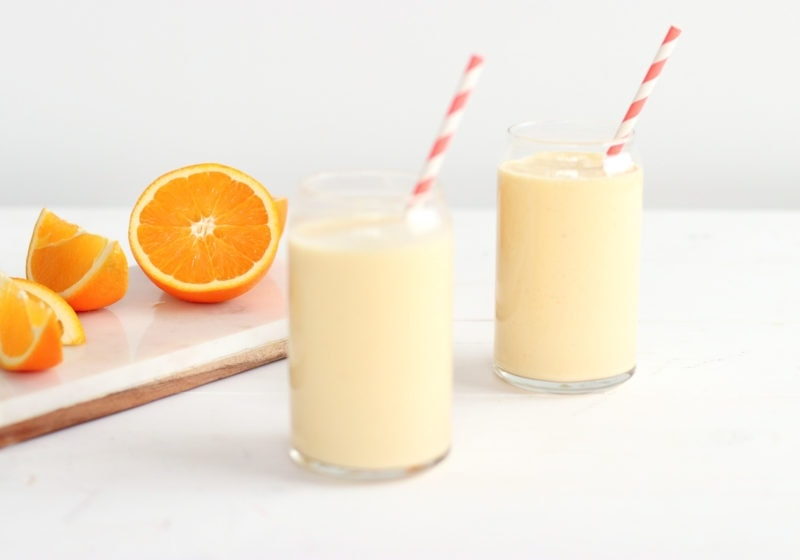 Hangover cure smoothie divided into two glasses with a white and pink striped straw on a white surface. Next to the two smoothies is a cutting board with a cut up orange on it.