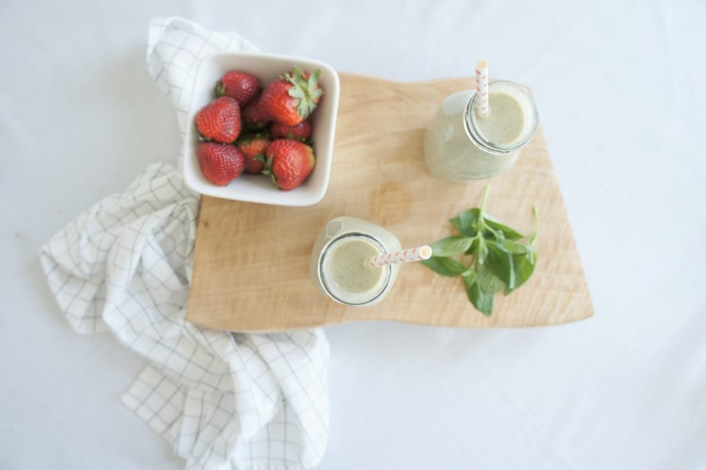 Strawberry Basil Smoothie over a white surface on a wooden food board with a checkered white kitchen towel beside it. Ingredients include strawberries, plain Greek yogurt, chia seeds, coconut flakes, basil.
