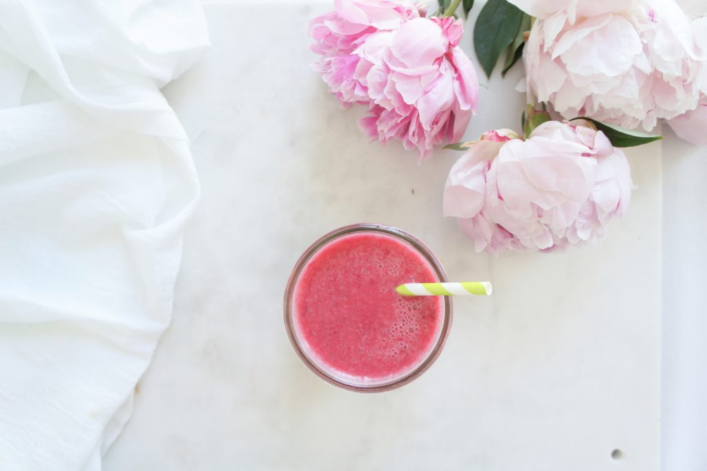 A pink smoothie with a green a white straw over a white surface with a bunch of peonies beside it.