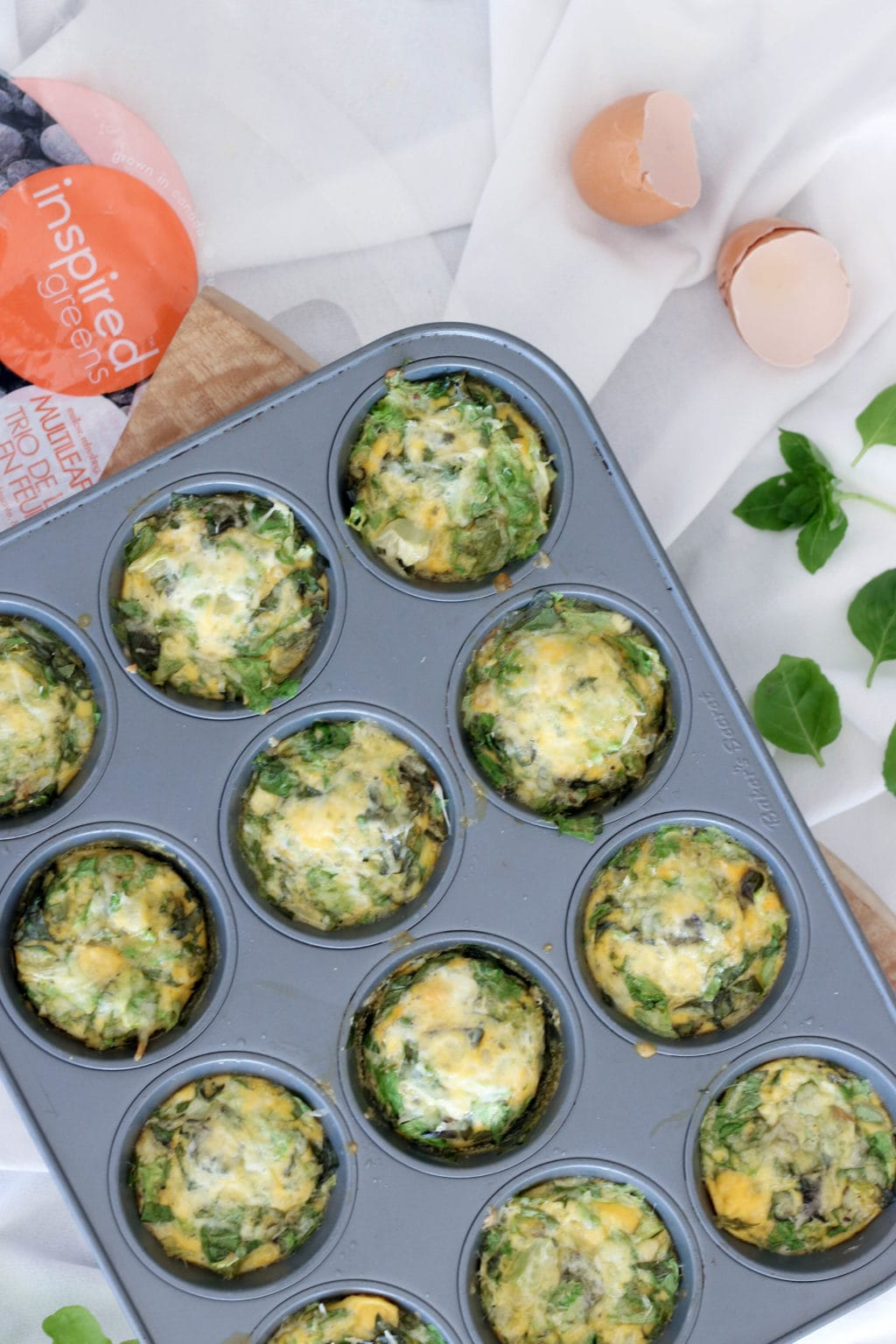 Muffin tin frittatas in a medium sized muffin tin over a white sheet with a bag of inspired greens beside it and a cracked egg. Ingredients include eggs, butter, greens, basil, cheese.